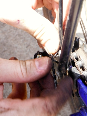 Adam trying to fix his bike with a bobby pin and a paper clip
