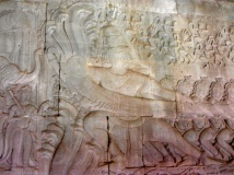 This particular bas-relief is quite famous and depicts the Hindu myth of the Churning of the Sea of Milk. By pulling alternately on the body of a naga (mythical snake-like creature with 7 heads) which is coiled around a mountain, the gods and the demons rotate the mountain for 1000 years churning the sea of milk and creating the elixir of immortality. This seems to be a commonly depicted story throughout the grounds of Angkor. All of the banisters of the major temples are made up of the gods/demons lined up and pulling on the naga.